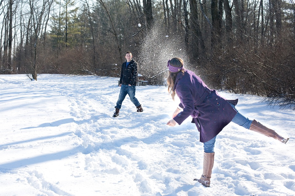 A couple throwing snowballs at each other