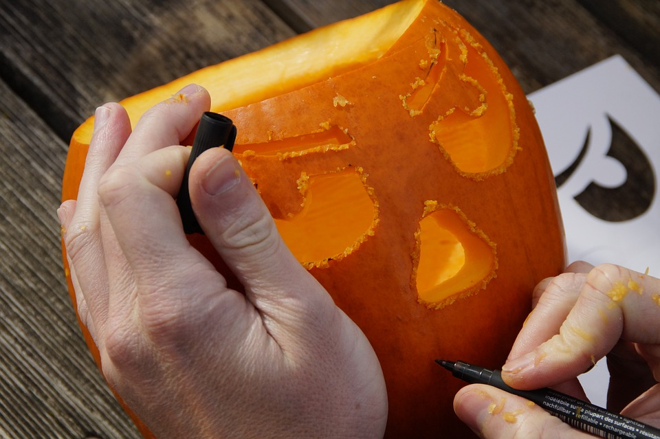 Person carving a design onto a pumpkin