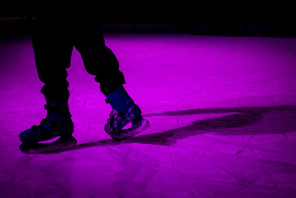 Person ice skating in purple light