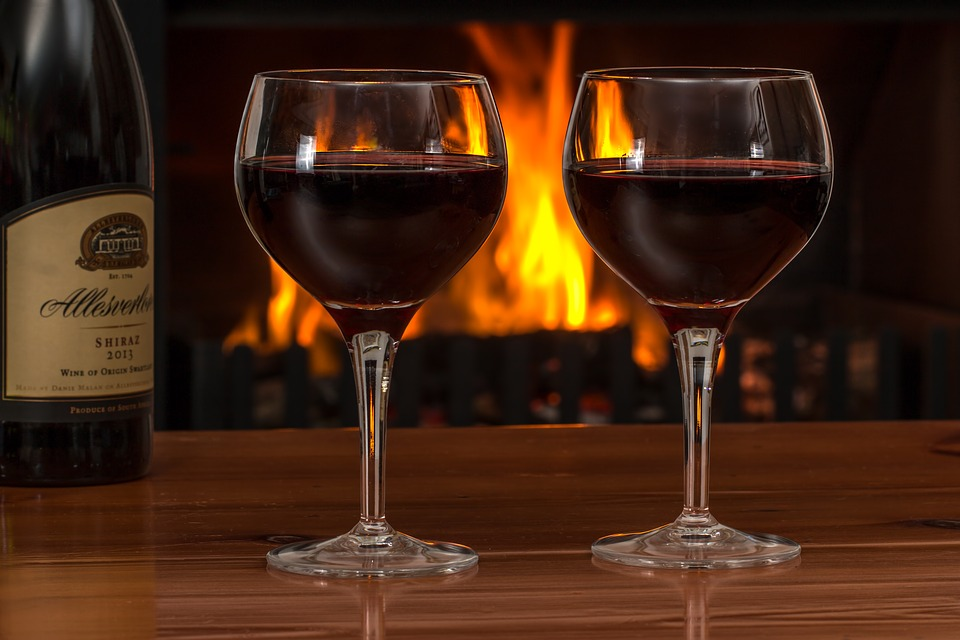 Two wine glasses in front of a log fire